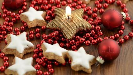 Weihnachten. Kerze mit Zimtsternen und Weihnachtskugeln