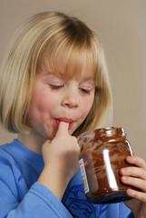 Niña golosa comiendo crema de chocolate.