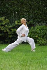 Señora feliz haciendo ejercicios en un jardín.