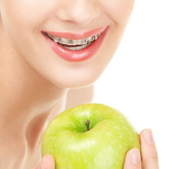 Girl in braces with green apple on white background