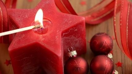 Sternförmige Kerze wird angezündet. Weihnachtsbaumkugeln.