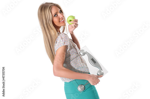 Young girl eating apple and carrying set of scales
