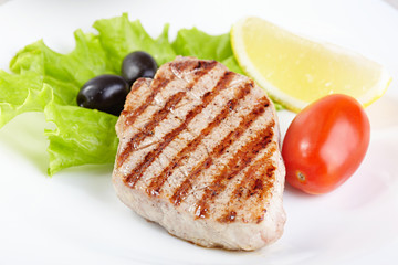 Grilled steak on white plate closeup