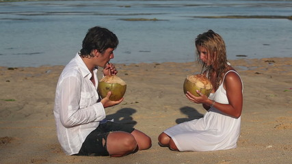 Attractive couple drinking coconuts and sitting on beach