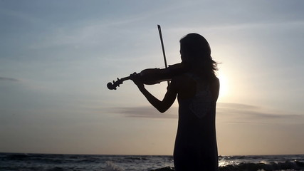 Silhouette of violinist playing on violin at ocean beach