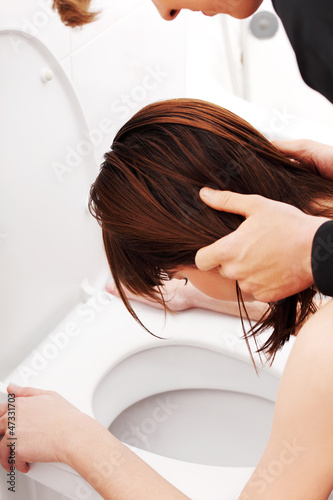 Boy holding his girlfriend head above toilet.