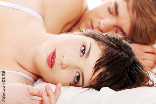 Beautiful young couple sleeping in bed.