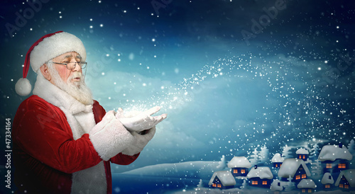Santa Claus blowing snow to little town