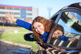 Joyous woman waving by hand from car window