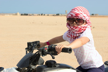 Small child in head kerchief and sunglasses on quadbike