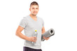A male holding a bottle and mat after an excerise