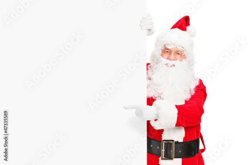 Santa claus posing next to a blank billboard and pointing