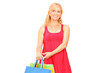 A smiling mature woman holding shopping bags