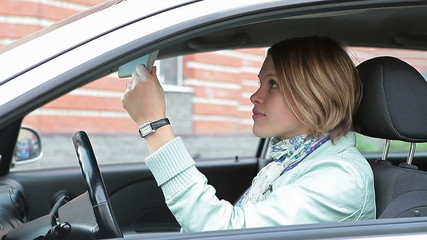 Young woman applying make-up sitting on driver`s seat in own car