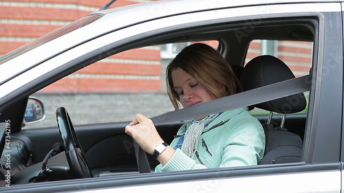 Blond female fastening a seat belt in vehicle