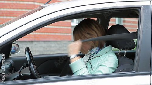 Young Caucasian woman sitting in car and fastening safety belt