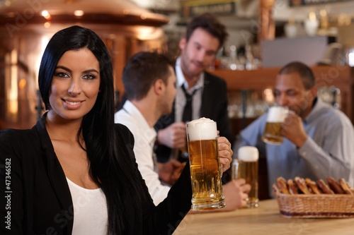 Young woman in pub with mug of beer