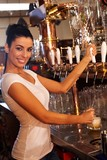Female bartender tapping draught beer in pub