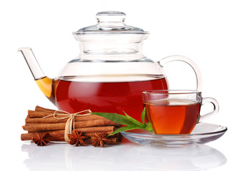 Teapot and cup of tea with green leaves and cinnamon sticks