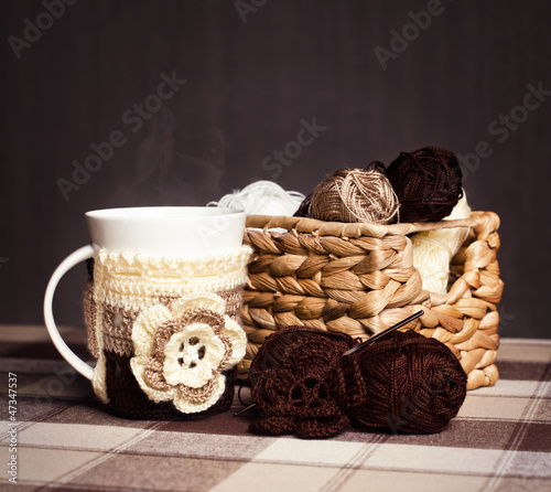 Crochet, skeins of yarn and cup of coffee on a dark background