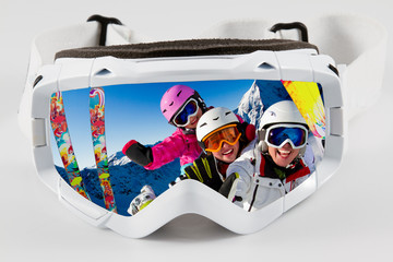 Skiing, winter - reflection in goggles of  skiing family