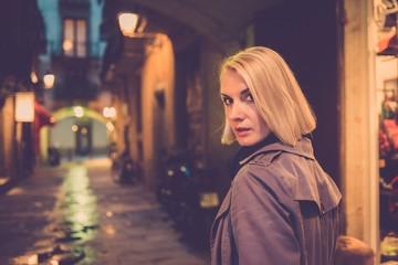 Beautiful blond woman in raincoat walking alone