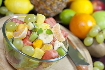 Fresh fruits salad in bowl in kitchen closeup