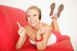 junge Frau auf einer roten Couch