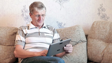 Mature adult sitting with tablet computer on divan