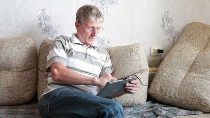 Mature adult Caucasian working with tablet pc at domestic sofa