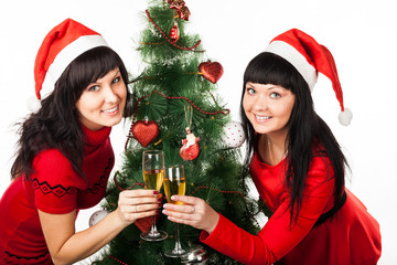 Two girls with champagne near Christmas tree