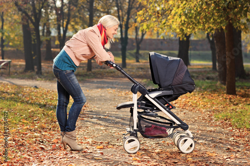 Smiling mother looking at her child in a baby stroller