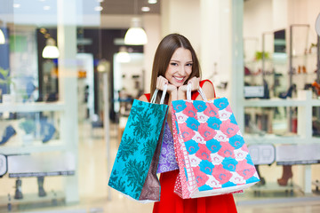 young woman posing with shopping bags in mall