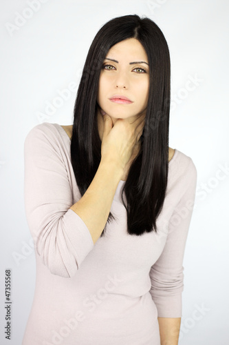 Serious beautiful woman sick with throat problem sore