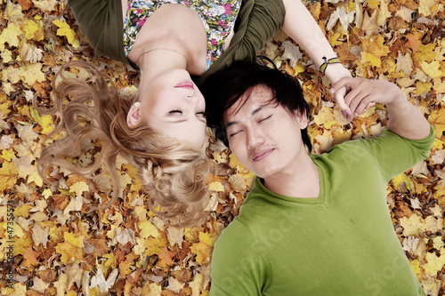 Beautiful loving couple sleep on autumn leaves