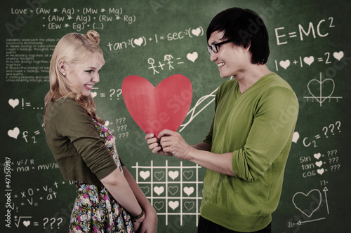 Cute nerd guy and girl holding heart in classroom