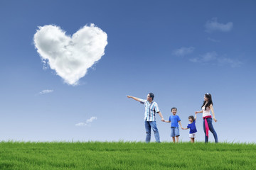 Happy family see clouds of love in the park