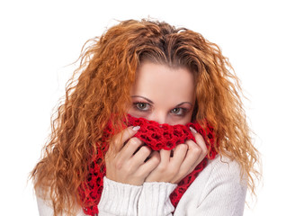 red-haired girl covers her face with scarf