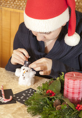 Cute smiling girl making cotton-wool snowman-selective focus