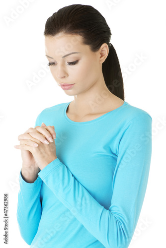 Portrait of a young caucasian woman praying