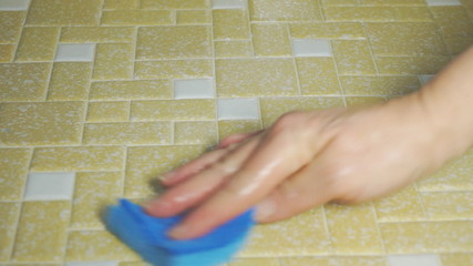 Person scrubbing floor with sponge close up