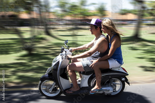 Happy couple traveling on moped