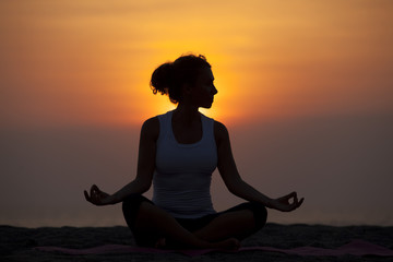 Slim woman meditating in pose lotus at evening