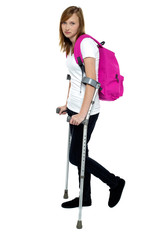 Teenager student holding crutches and walking