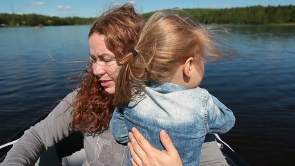 Mother and child moving fast on motorboat bow on the river