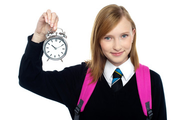 Pretty charming schoolgirl holding time piece