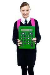 School girl holding large green calculator