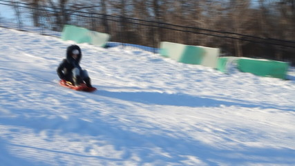 Woman having fun sledding down hill in the snow