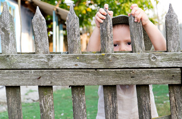 Boy looking through a fence