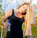 Perspiring woman athlete wiping her brow poster